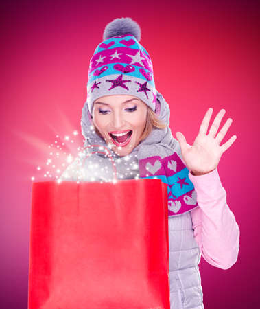 Photo of the happy surprised woman with gifts after shopping to the new year at shop Stock Photo - 23233363