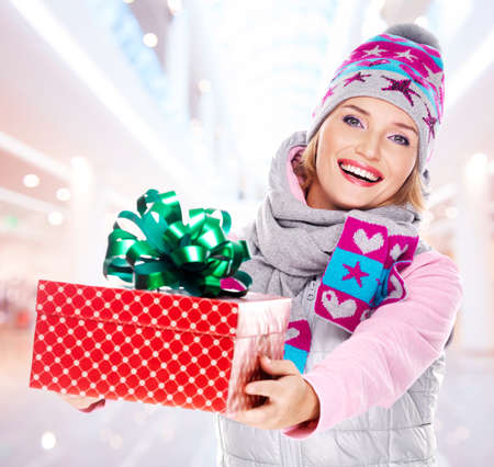 birthday presents: Photo of young adult woman gives the christmas  gift dressed in a winter outerwear  - indoors