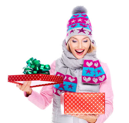 Photo of happy surprised woman with a christmas gift in a winter outerwear - isolated on white photo