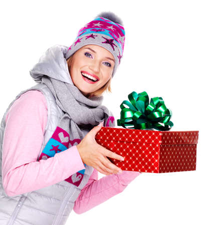 Photo of happy adult woman giving a christmas gift in a winter outerwear - isolated on white photo
