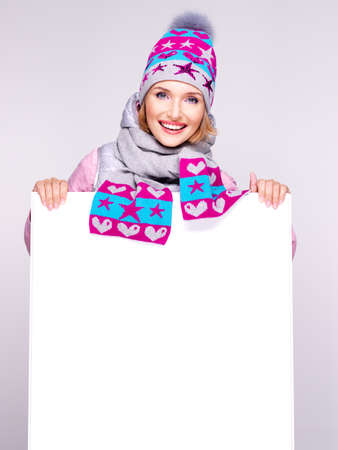 winter woman:  Smiling  woman in winter outerwear holds the white banner in hands at studio