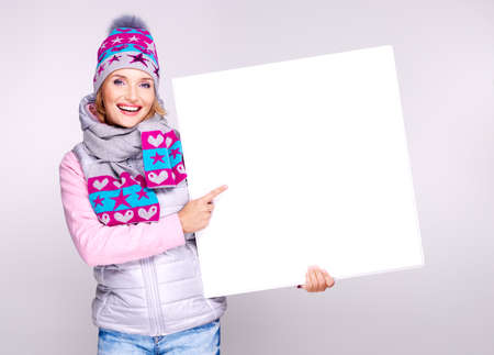 Adult smiling  woman in winter hat holds the white banner in hands at studio Stock Photo - 22680922