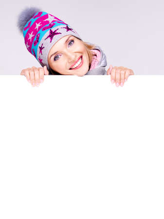 winter woman: Happy  woman in winter outerwear over white banner in hands at studio