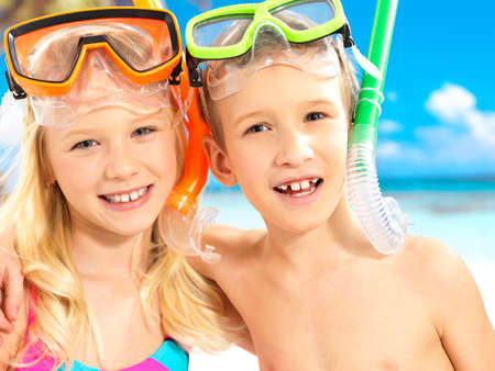 Portrait of the happy children enjoying at beach.  Brother and sister standing together in swimwear with swimming mask on head .  photo