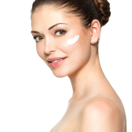 woman face cream: Young woman with cosmetic  cream on a clean fresh face