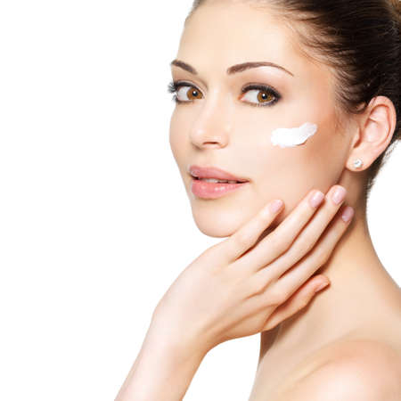 beautiful skin: Young woman with cosmetic  cream on a clean fresh face. Skin care concept