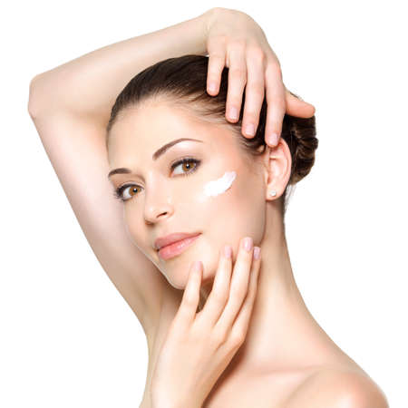 woman face cream: Young woman with cosmetic  cream on a clean fresh face. Skin care concept