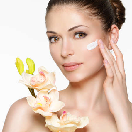 woman face cream: Young woman with cosmetic  cream on a clean fresh face. Healthy lifestyle concept LANG_EVOIMAGES