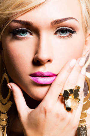 Closeup portrait of beautiful face of sexy woman with fashion makeup and gold ring on finger Stock Photo - 23233403