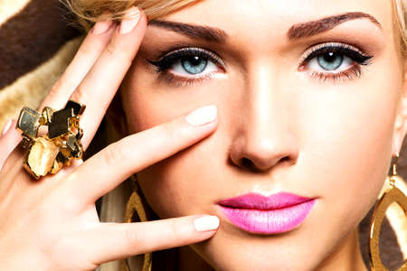 Closeup portrait of beautiful face of sexy woman with fashion makeup and gold ring on finger Stock Photo - 23233404