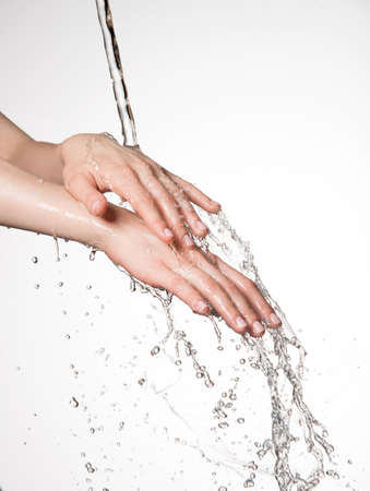 lavare le mani: Mani femminili del primo piano sotto il flusso di spruzzi d'acqua - concetto di cura della pelle