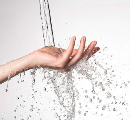 falling water: Closeup woman hand under the stream of splashing water - skin care concept LANG_EVOIMAGES