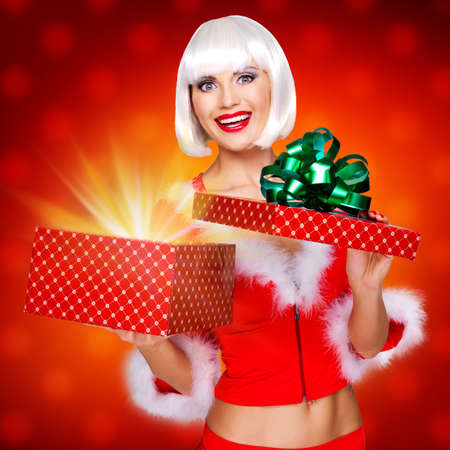 happy birthday girl: Photo of surprised snow maiden with a christmas gift with magic shining from box - studio red background