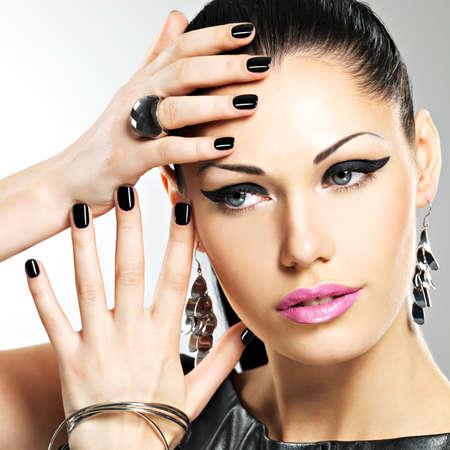 Belle femme de mode sexy avec des ongles noirs au joli visage. Modèle Pretty girl with bijouterie élégant de couleur argent.