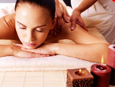 mimos: Masajista haciendo masaje en el cuerpo de la mujer en el salón de spa. Belleza concepto de tratamiento.