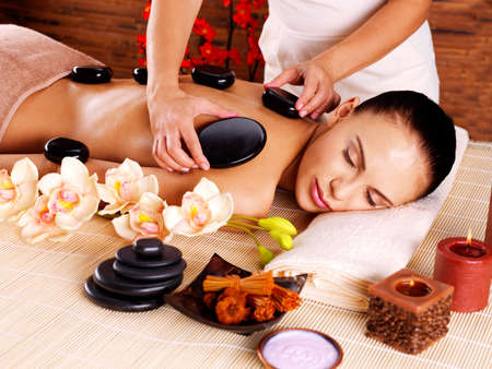 woman spa: Adult woman having hot stone massage in spa salon. Beauty treatment concept.