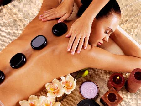 adultos: Mujer adulta que tiene masaje de piedra caliente en el sal�n de spa. Concepto de tratamiento de belleza.