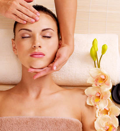 spa therapy: Masseur doing massage the head of an adult woman in the spa salon