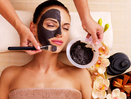 beauty salon: Cosmetologist smears cosmetic mask on the face of the woman in the sap salon