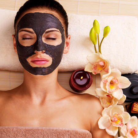 vertical wellness: Adult woman relaxing in spa salon. Female face with cosmetic mask. Beauty treatment