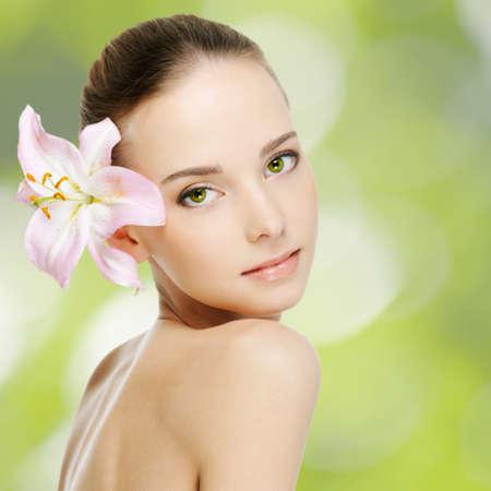 美しい若い女性の健康皮膚と花 写真素材
