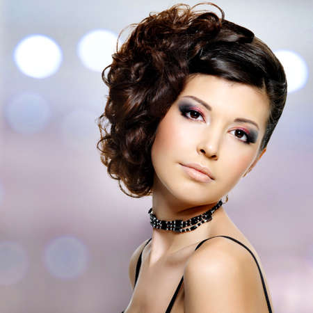 Beautiful young woman with fashion hairstyle and bright makeup  photo
