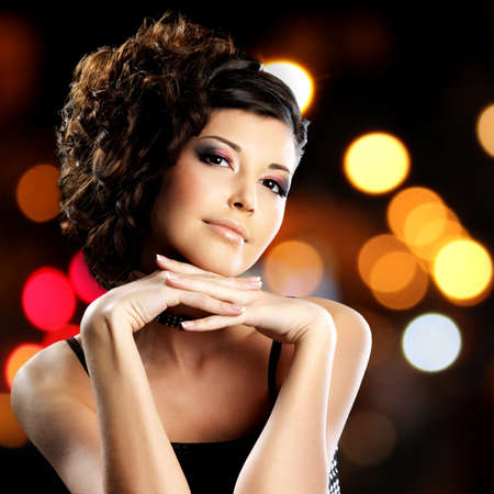 Portrait of brunette woman with fashion hairstyle over night lights bokeh background photo