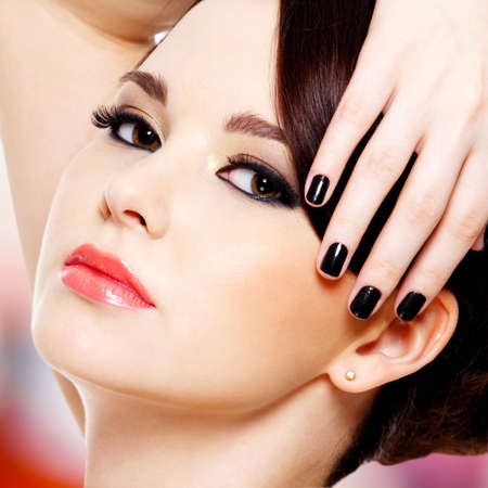Face of the beautiful young woman with black nails looking at camera photo