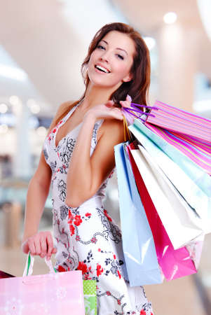 shopping bags: Happy beautiful woman with shopping bags stands at shop Stock Photo