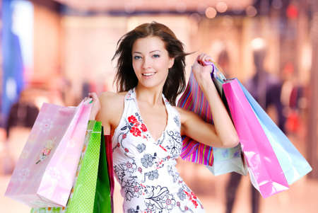 Happy beautiful woman with shopping bags stands at shop photo