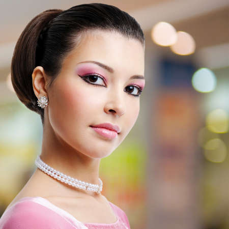 Face of beautiful woman with fashion hairstyle and glamour makeup - over creative soft bokeh background photo