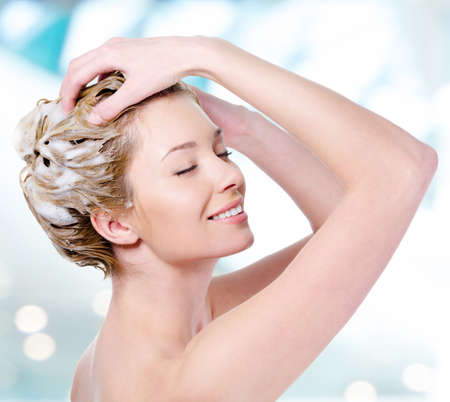 샴푸: 그녀의 머리를 비누 칠 매력적인 미소와 아름 다운 젊은 금발 여자 - 흰색 배경에 고립 스톡 사진