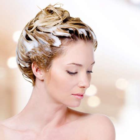 Mooie jonge vrouw met inzepen hoofd en gesloten ogen - geïsoleerd op wit