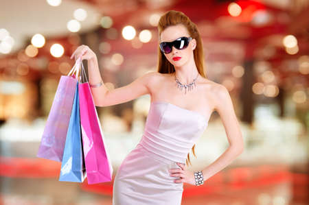shopaholics: Beautiful fashion woman with shopping bags stands at shop