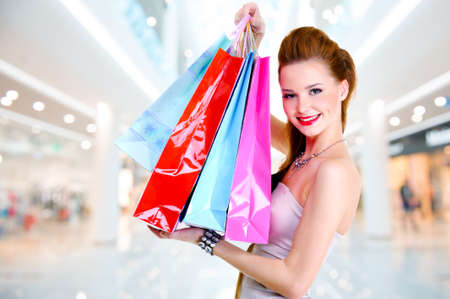 Happy beautiful woman with shopping bags stands at shop Stock Photo - 22997134