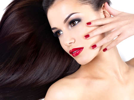 Beautiful woman with long brown straight hairs and elegance red nails photo