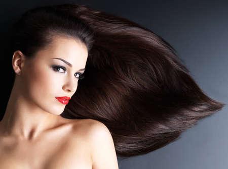 chicas guapas: Mujer joven con los pelos marrones largos rectos sobre un fondo oscuro Foto de archivo