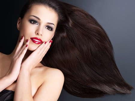 Beautiful woman with long brown straight hairs and red nails lying on the dark background photo