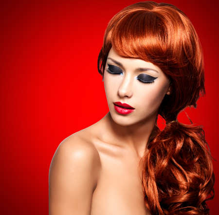 colours: Beautiful  woman with long red hairs and bright eye makeup -  over red background