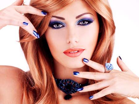 labios sexy: La cara del primer de una mujer hermosa sensual con las u�as de color azul, maquillaje azul y los labios rojos sexy sobre fondo blanco LANG_EVOIMAGES