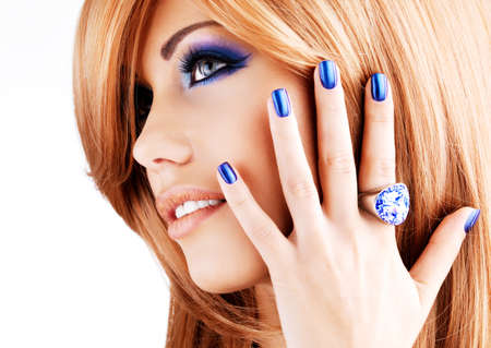 nail studio: portrait of a beautiful woman with blue nails, blue makeup and red hairs  on white  background
