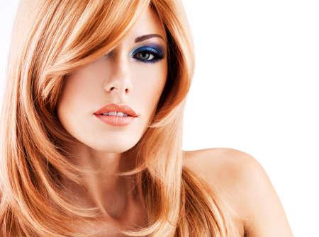 Gros plan portrait d'une belle femme avec de longs cheveux rouges et le maquillage des yeux bleu - isolé sur fond blanc LANG_EVOIMAGES