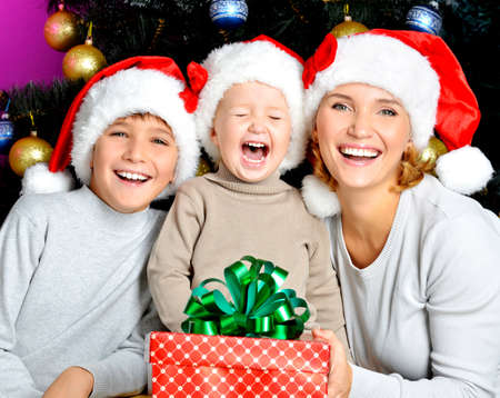 Happy mother with children holds the new year gift on the christmas holiday - indoors Stock Photo - 23233585