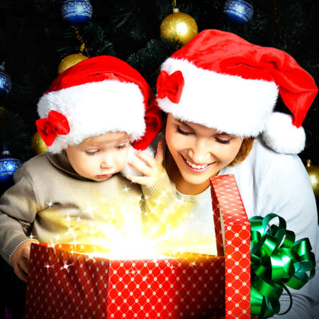 baby open present: Mother with little child opens the box with gifts on the christmas holiday - indoors
