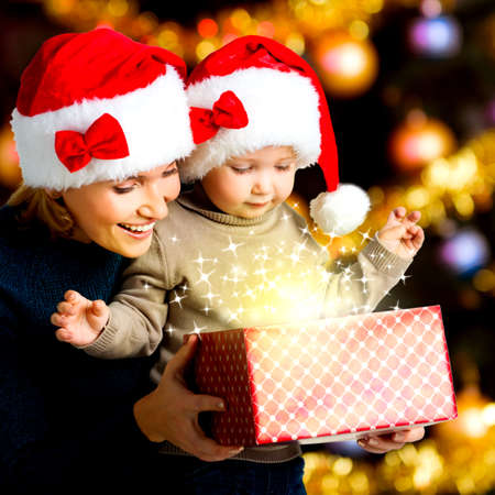 Mother with little child opens the box with gifts on the christmas holiday - indoors Stock Photo - 23233594