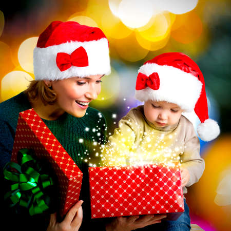 Mother with little child opens the box with gifts on the christmas holiday - indoors Stock Photo - 23233595