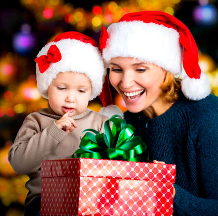 baby open present: Smiling mother with little child hold box with new year gifts on the christmas holiday - indoors