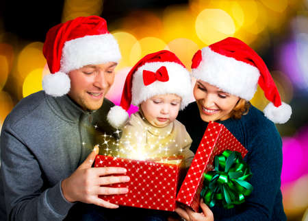 Happy familiy with one baby opens the  box with christmas gifts on the new year  holiday - indoors Stock Photo - 23233598