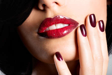 human fingernail: Closeup face of a woman with beautiful sexy red lips and dark nails - studio LANG_EVOIMAGES