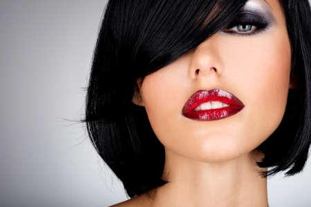 ショットの髪型とセクシーな赤い唇と美しいブルネットの女性。ファッション化粧と女性モデルのクローズ アップの肖像画